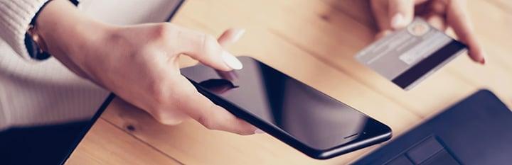 femme utilisant sa carte de néobanque avec son smartphone