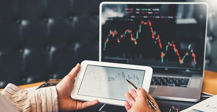 Graphiques boursiers sur une tablette et un écran de PC