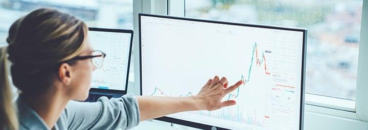 femme analysant un graphique boursier sur son PC