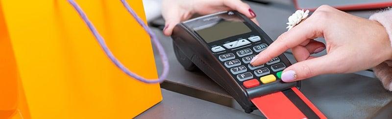 cliente utilisant un terminal de paiement en boutique